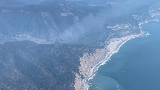 A wildfire smolders along the North Coast