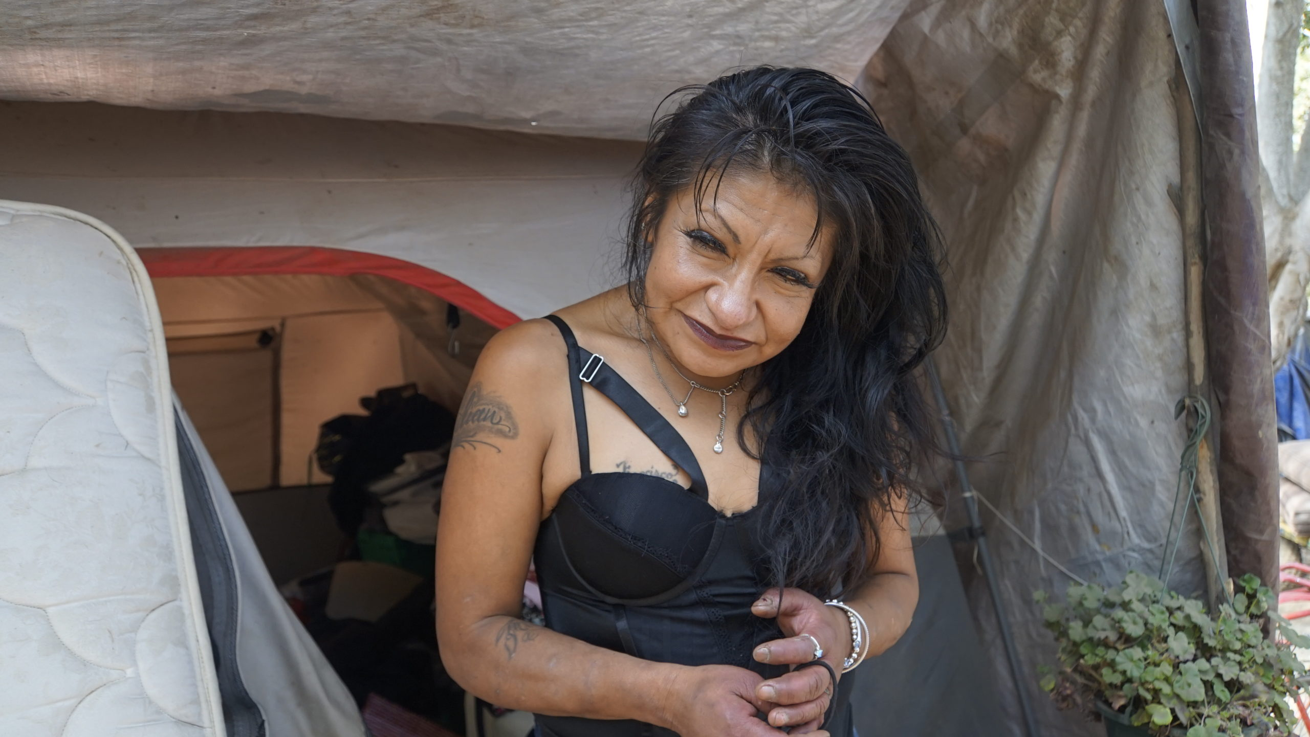 Julissa Diaz stands next to her tent at Camp Paradise in Santa Cruz in September 2021